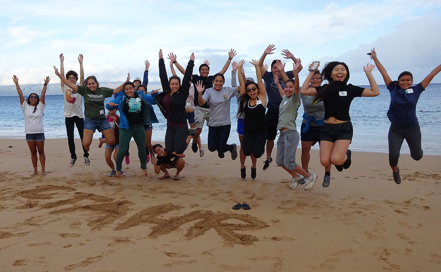 Group of CTAHR students jumping in the air at the beach.