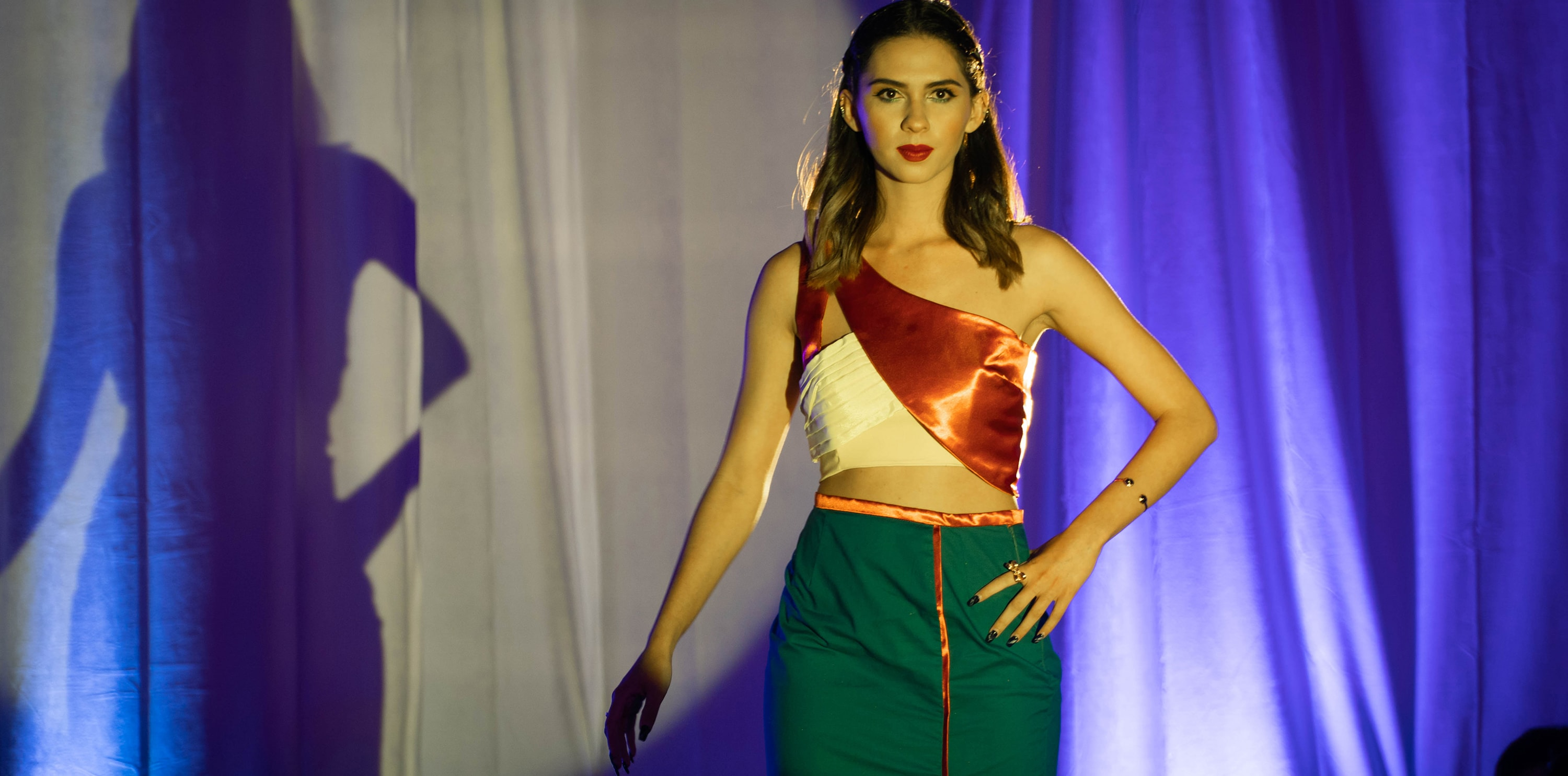 Model on a fashion runway wearing a red and white off the shoulder top with a green dress skirt.