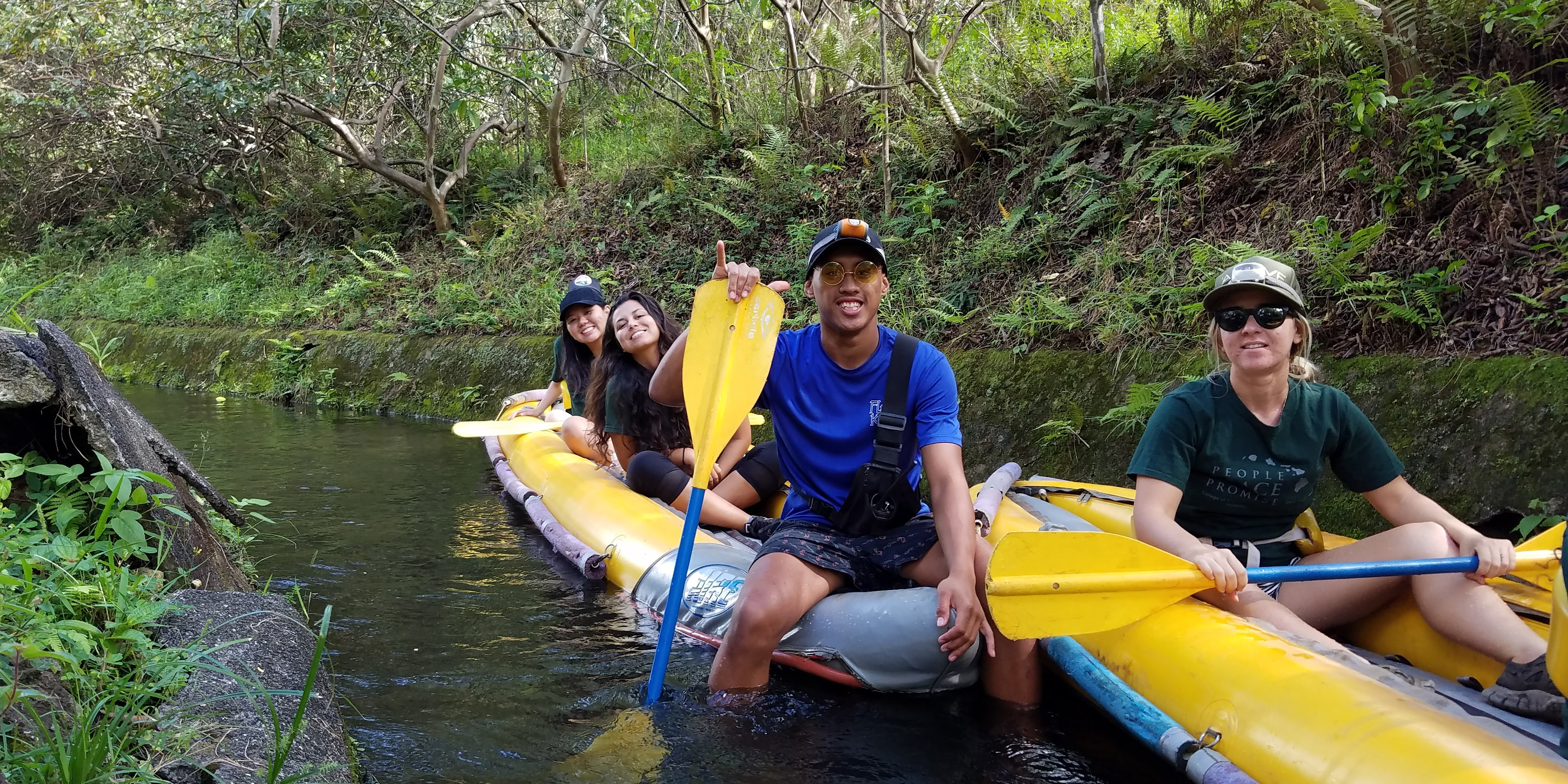 Students floating through an irrigation ditch on inflatable boats.